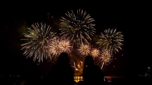 Mensen kijken naar prachtig vuurwerk samen door de zee 's nachts.