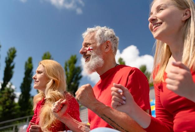 Mensen kijken samen naar een voetbalwedstrijd op een zonnige dag