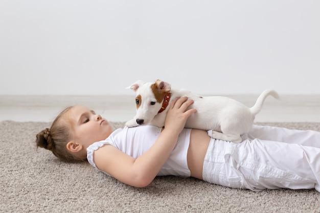 Mensen kinderen en huisdieren concept klein kind meisje liggend op de vloer met schattige puppy in handen
