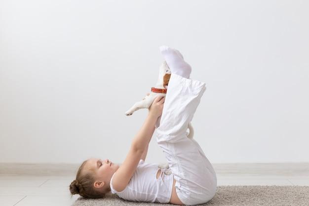 Mensen, kinderen en huisdieren concept - klein kind meisje liggend op de vloer met schattige puppy jack russell terrier
