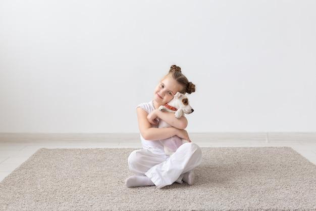Mensen kinderen en huisdieren concept klein kind meisje zittend op de vloer met schattige puppy jack russell