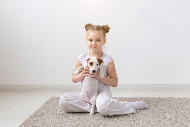 Mensen, kinderen en huisdierenconcept - klein kindmeisje dat op de vloer ligt met schattige puppy jack russell terrier
