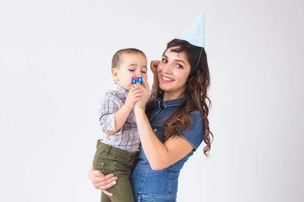 Mensen, kinderen en vakantieconcept - charmante moeder houdt haar zoon die verjaardagspet over wit draagt