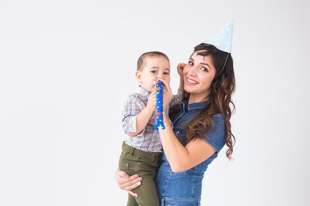 Mensen, kinderen en vakantieconcept - charmante moeder houdt haar zoon met verjaardagspet over witte muur met exemplaarruimte.