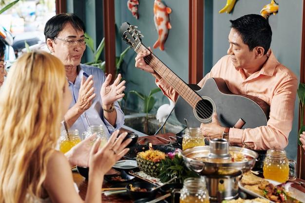 Mensen klappen naar vriend gitaar spelen
