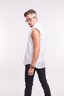 Mensen, kleding en stijl concept - jonge knappe man poseren in wit overhemd op wit oppervlak