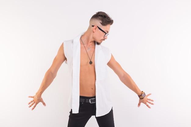 Mensen, kleding en stijlconcept - het jonge knappe mens stellen in wit overhemd op witte muur