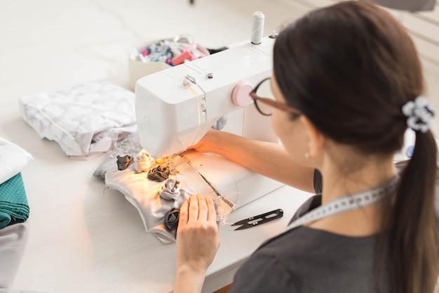 Mensen, kleermaker en mode-concept - close-up portret van werkplek modeontwerper met naaimachine.