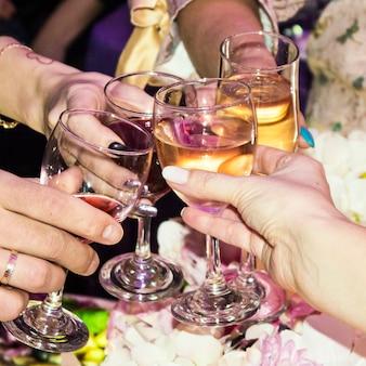 Mensen klinken glazen met rode en witte wijn. glazen wijn in vrouwenhanden, vrouwelijk alcoholisme, vrouwenvakantie