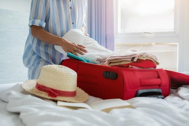 Mensen koffer met reisaccessoires op bed ingepakt.
