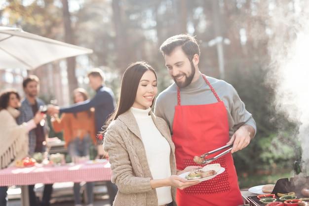 Mensen koken barbecuevoedsel tijdens een picknick.