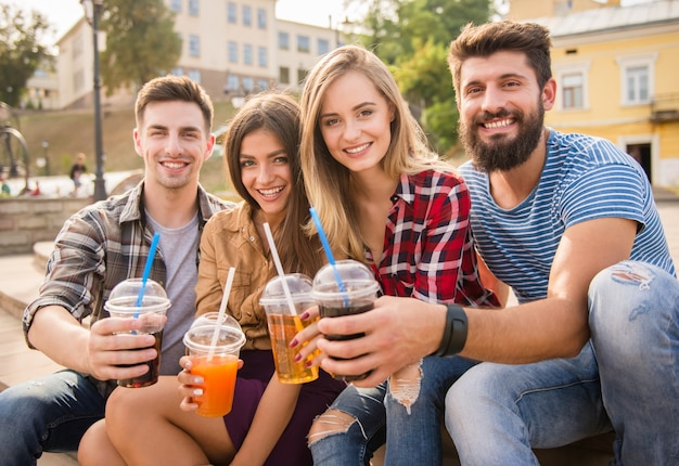 Mensen lachen samen en drinken sap op straat.
