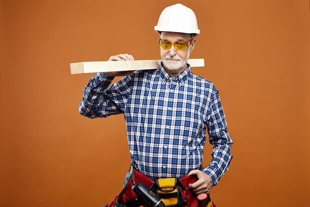 Mensen, leeftijd, baan en beroep concept. portret van zelfverzekerde gerichte senior man met gele bril, geruite shirt, veiligheidshelm en wiast tas met gereedschap, houten balk op zijn schouder dragen