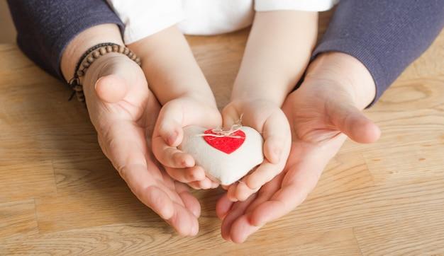 Mensen, leeftijd, familie, liefde en gezondheidszorgconcept - sluit omhoog van hogere vrouw en weinig jongenshanden houdend rood hart over houten achtergrond