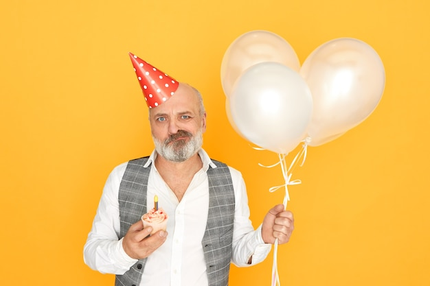 Mensen, leeftijd, feest en vakantieconcept. horizontale opname van chagrijnige oudere zakenman poseren geïsoleerd met ballonnen, kegel hoed en cupcake, viert zijn pensioen, ontevreden blik