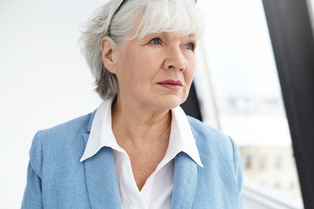 Mensen, leeftijd, levensstijl, mode en pensioenconcept. foto van elegante modieuze zestig-jarige zakenvrouw met gerimpeld gezicht en wit haar na te denken over zakelijke kwesties, die zich voordeed bij raam