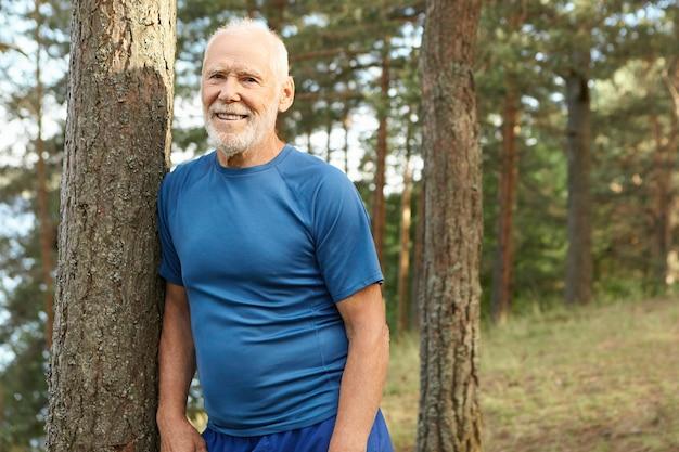 Mensen, leeftijd, pensioen, fitness en sport. zomerbeeld van positieve gelukkige zeventig-jarige mannelijke gepensioneerde die op adem komt tijdens het uitvoeren van oefening in dennenbos