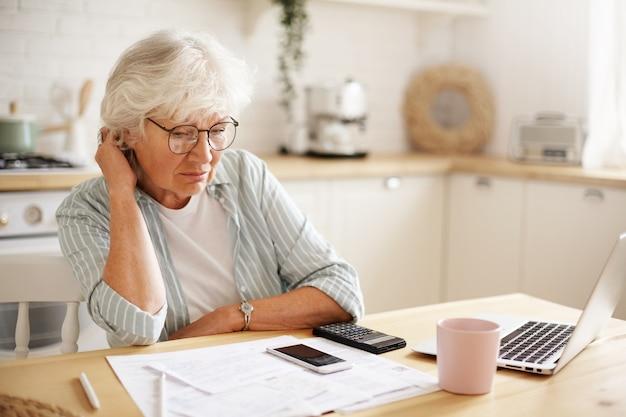 Mensen, leeftijd, technologie en financiën. depressieve, ongelukkige gepensioneerde vrouw die binnenlandse rekeningen online betaalt, hard probeert om beide eindjes aan elkaar te knopen, zittend aan de keukentafel, omringd met papieren, met behulp van gadgets