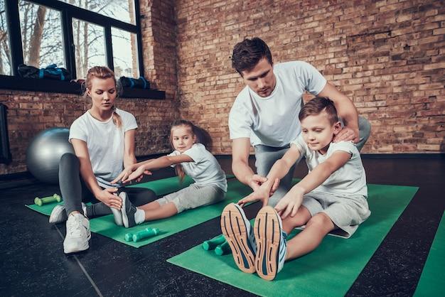 Mensen leren kinderen die zich uitstrekken in de sportschool