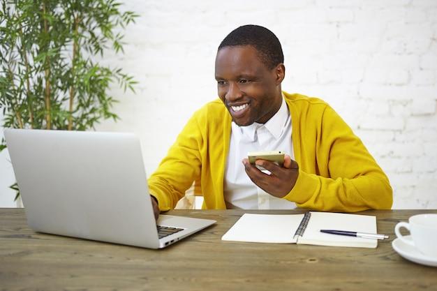 Mensen, levensstijl, baan, technologie en communicatieconcept. vrolijke afro-amerikaanse mannelijke freelancer in helder geel vest met behulp van mobiele telefoon en draagbare computer in kantoor aan huis, breed glimlachend