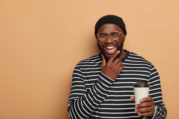 Mensen, levensstijl, emoties concept. vrolijke zwarte man houdt kin, lacht oprecht, drinkt afhaalkoffie