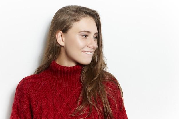 Mensen, levensstijl en gezelligheid concept. aantrekkelijke charmante jonge vrouw warme gebreide trui dragen op koude winterdag, tijd thuis doorbrengen