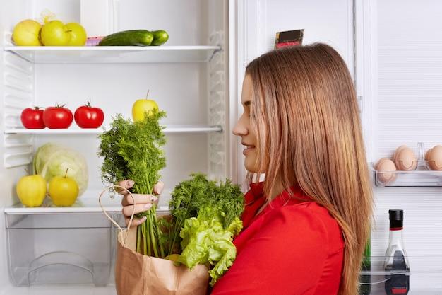Mensen, levensstijl en gezond eten concept. zijwaarts schot van schattige vrouw houdt papieren doos met dille en sla, heeft een koelkast vol met groenten en fruit, gaat vegetarische verse salade maken