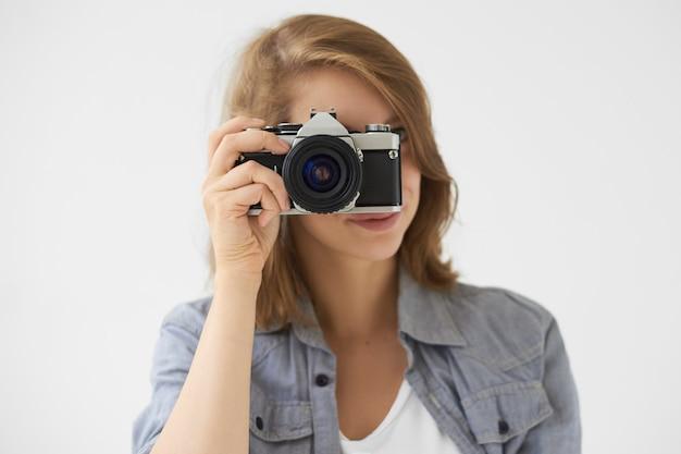 Mensen, levensstijl en technologieconcept. studio shot van stijlvolle meisje met rolfilm camera op haar gezicht, foto van jou nemen. jonge vrouwenfotograaf die uitstekend apparaat gebruikt om foto te nemen