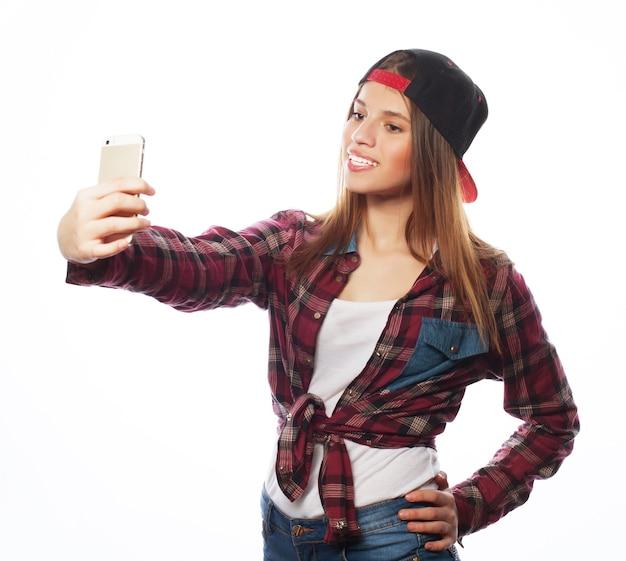 Mensen, levensstijl en tehnologyconcept: mooi tienermeisje dat hoed draagt, selfies neemt met haar slimme telefoon - die op wit wordt geïsoleerd
