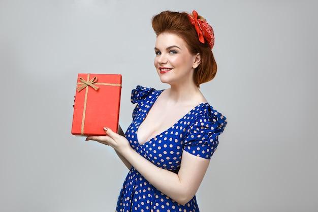 Mensen, levensstijl en vakantieconcept. studio shot van vrolijke jonge europese huisvrouw in stijlvolle vintage kleding die zich gelukkig voelt, rode doos vasthoudt, zich verheugt op verjaardagscadeau
