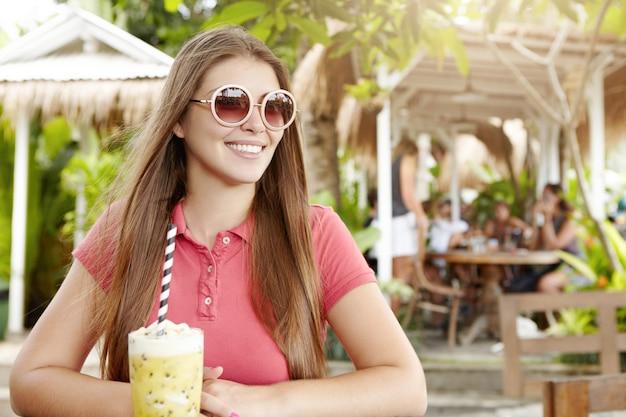Mensen, levensstijl en vrije tijd. vrolijke jonge vrouw gekleed in poloshirt zit in café met fruit shake op tafel.