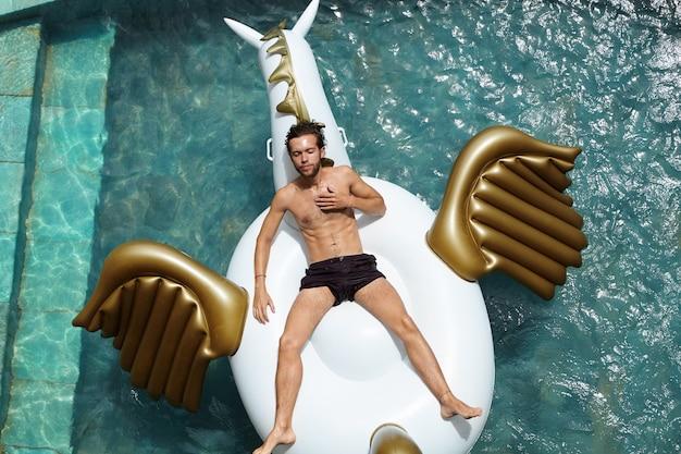 Mensen, levensstijl en zomervakanties concept. zelfverzekerd aantrekkelijk mannetje dat zwarte zwembroek draagt, ontspant in het buitenzwembad, drijft op een opblaasbaar matras en geniet van gelukkige en zorgeloze dagen