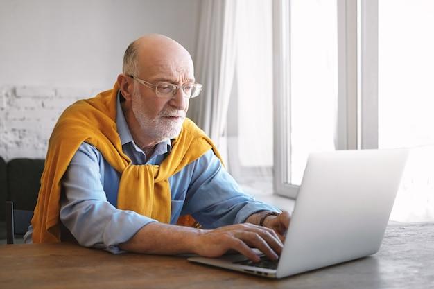 Mensen, levensstijl, leeftijd, bedrijf, baan, carrière en beroepconcept. binnen schot van gerichte serieuze mannelijke kantoormedewerker in glazen, blauw shirt en trui keyboarding op generieke laptop, snel typen