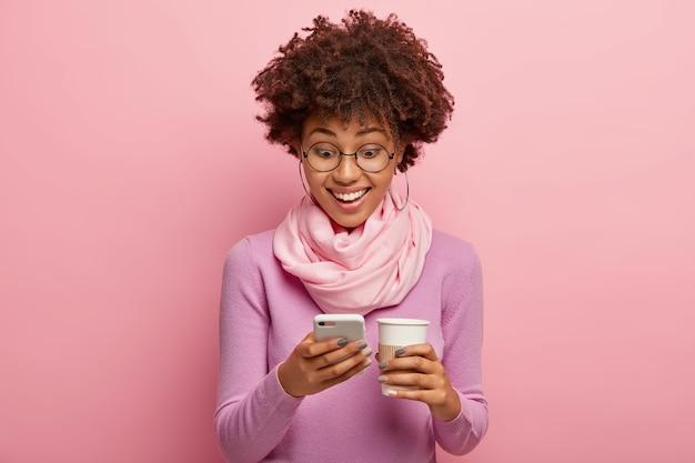 Mensen, levensstijl, online communicatieconcept. vrolijke donkere vrouw typt tekstberichten op de mobiele telefoon