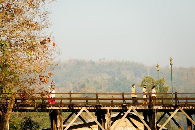 Mensen levensstijl op sangklaburi of myanmar hoge houten brug over de rivier songaria, beroemde toeristische bestemming prachtig uitzicht en lokale traditionele cultuur.