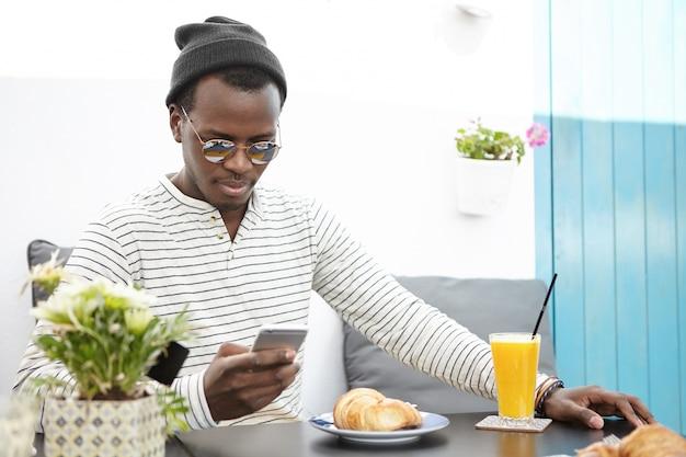Mensen, levensstijl, reizen, vakanties en moderne technologie concept. knappe donkere toerist dragen van stijlvolle hoed en zonnebril sms'en op mobiele telefoon tijdens het ontbijt op terrasje