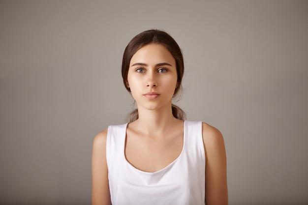 Mensen, levensstijl, schoonheid en modeconcept. close-up portret van mooie stijlvolle jonge europese vrouw poseren geïsoleerd met kalme vreedzame gezichtsuitdrukking dragen witte mouwloze top