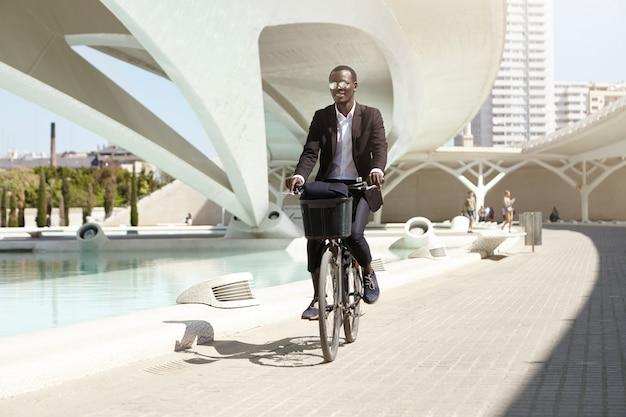Mensen, levensstijl, transport en ecologie. knappe vrolijke glimlachende jonge donkerhuidige geklede beambte die formeel pendelt om aan zijn retro zwarte fiets te werken, genietend van zonnige de zomerochtend