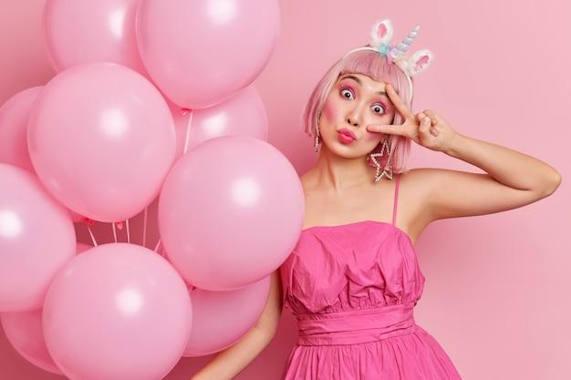 Mensen levensstijl viering vakantie concept. aziatische vrouw met bobkapsel kantelt hoofd heeft grappige blik gebaren overwinningsteken geniet van feest draagt stijlvolle jurk poses met ballonnen