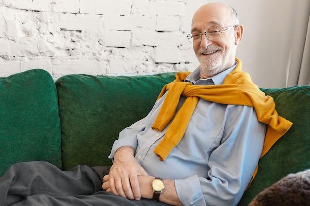 Mensen, levensstijl, vreugde, rust en ontspanningconcept. horizontaal schot van knappe emotionele 70-jarige grootvader die elegante kleding en bril draagt die thuis op de bank ontspant, breed glimlachend