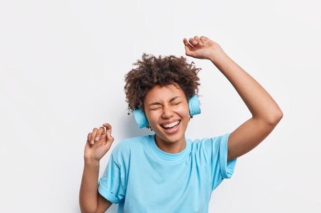 Mensen levensstijl vrije tijd concept. energieke vrolijke afro-amerikaanse vrouw met krullend haar danst zorgeloos steekt armen op voelt zich geamuseerd geniet van favoriete muziek draagt draadloze koptelefoon blauw t-shirt