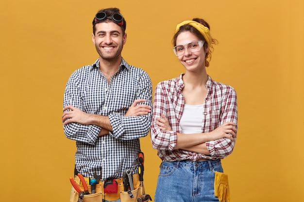 Mensen, levensstijl, werk en beroep concept. portret van gelukkige zelfverzekerde vrouwelijke elektrotechnicus in veiligheidsbril
