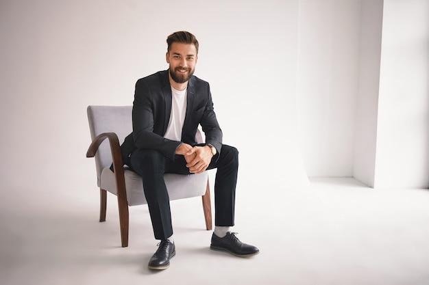 Mensen, levensstijl, zaken, stijl, mode en herenkledingconcept. positieve succesvolle jonge ceo zittend in een stoel, glimlachen, gekleed in elegante schoenen, broek, jas en wit t-shirt