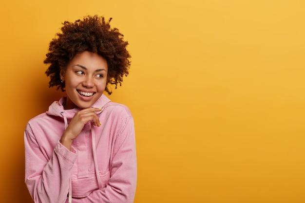 Mensen, levensstijlconcept. positieve donkere vrouw blij om goede kansen te vinden voor toekomstig werk, houdt kin vast kijkt weg met een brede glimlach hoort geweldig nieuws voelt vrolijk aan, poseert op gele muur