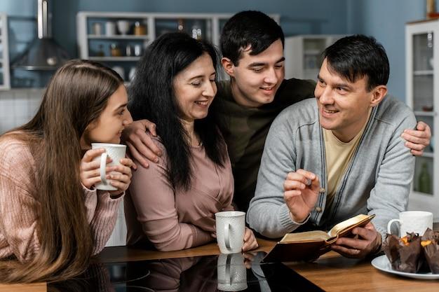 Mensen lezen uit de bijbel in de keuken