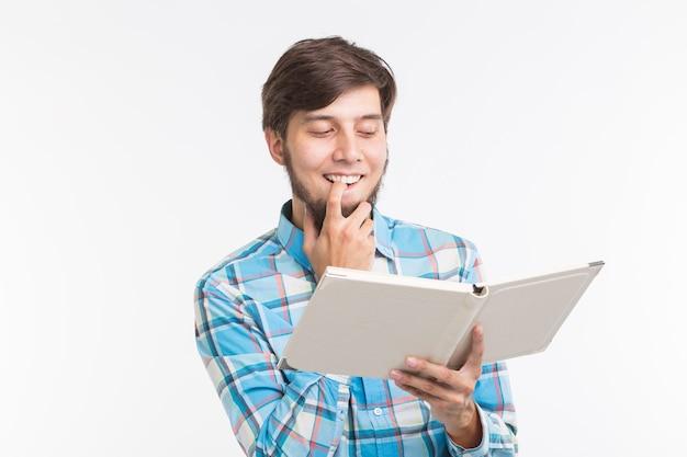 Mensen, lezing en onderwijsconcept - jonge mens die een boek op witte achtergrond leest