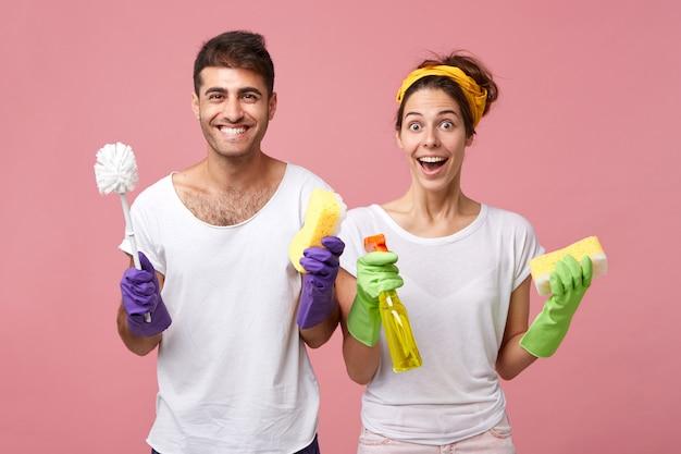Mensen, liefde, familie, relaties en huishoudelijke taken concept. gelukkig lachend jong europees koppel opgewonden en gelukkig