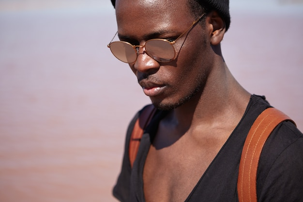 Mensen, lifestyle en mode concept. sluit omhoog portret van knap modieus jong afrikaans amerikaans mannelijk model met leerrugzak die modieuze zwarte t-shirt dragen en zonnebril die in openlucht stellen