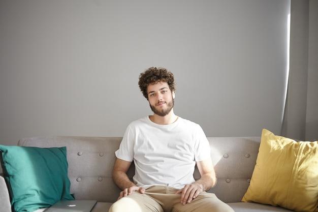 Mensen, lifestyle, interieur en designconcept. vrolijke aantrekkelijke jonge blanke man met stoppels en stijlvol golvend kapsel zittend op een comfortabele bank met decoratieve kussens en glimlachen