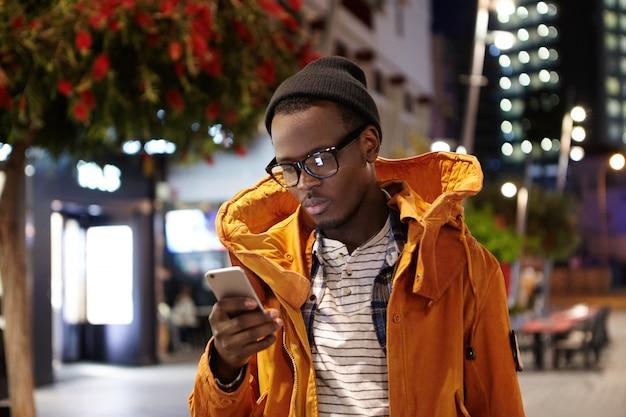 Mensen, lifestyle, reizen, toerisme en moderne technologie. vermoeide jonge afro-amerikaanse man die mobiele telefoon gebruikt voor het aanvragen van een taxi via de online taxiservice-app om na een lange vlucht naar het hotel te gaan